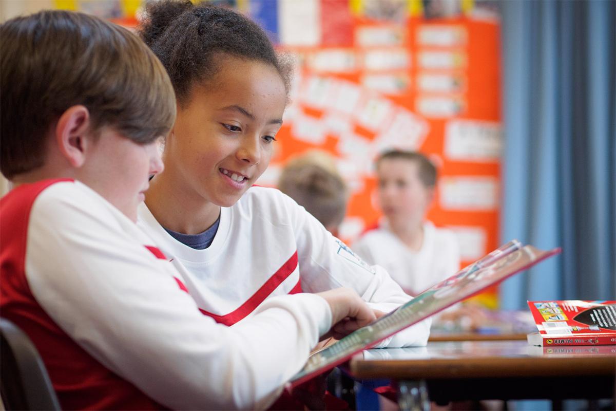 Pupils reading magazine in classroom.