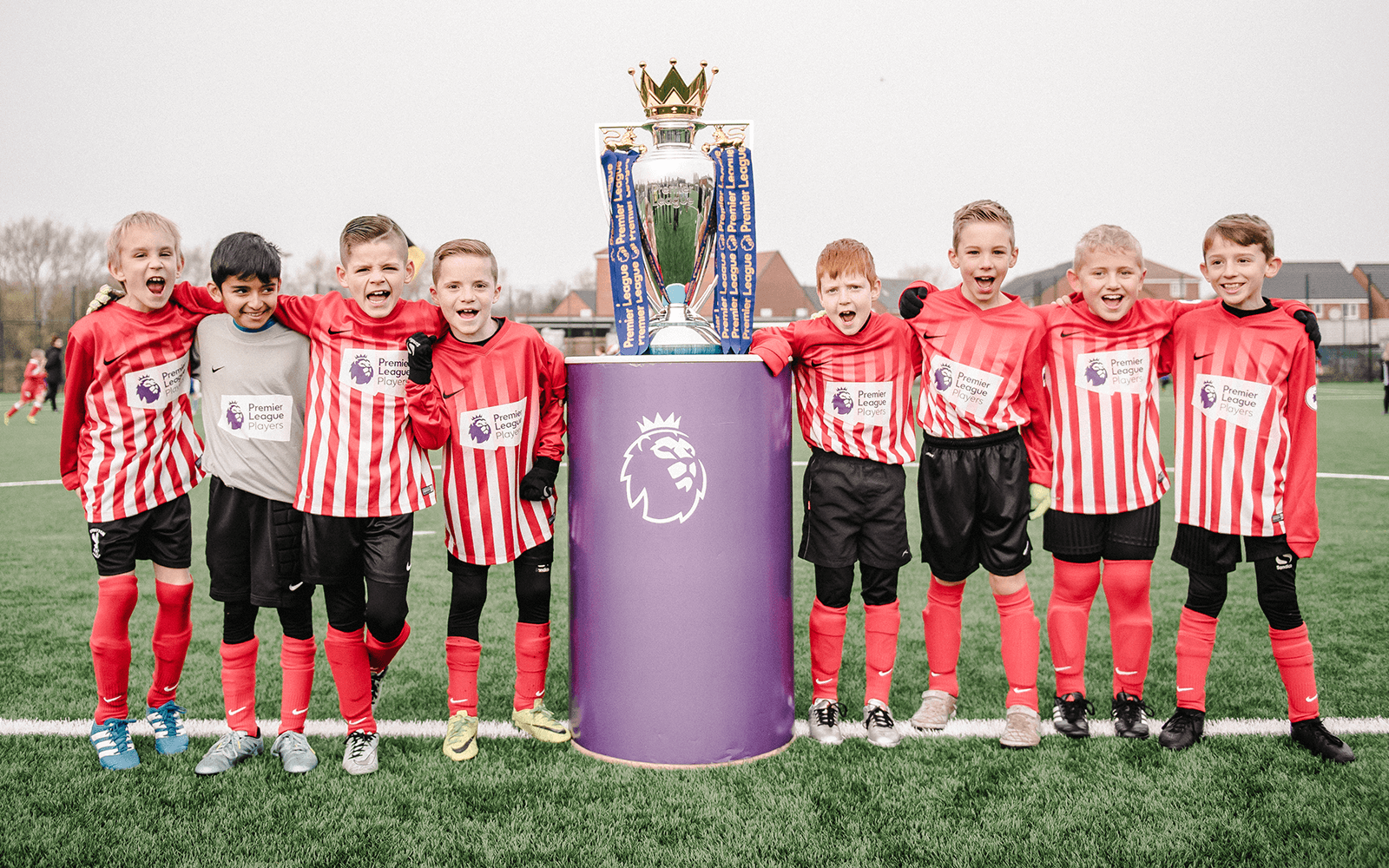 Pupils celebrating beside the Premier League trophy.