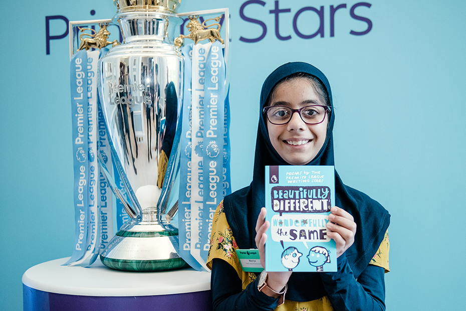 Key Stage 2 national winner Maariya standing next to the trophy holding up a copy of the writing stars poetry book
