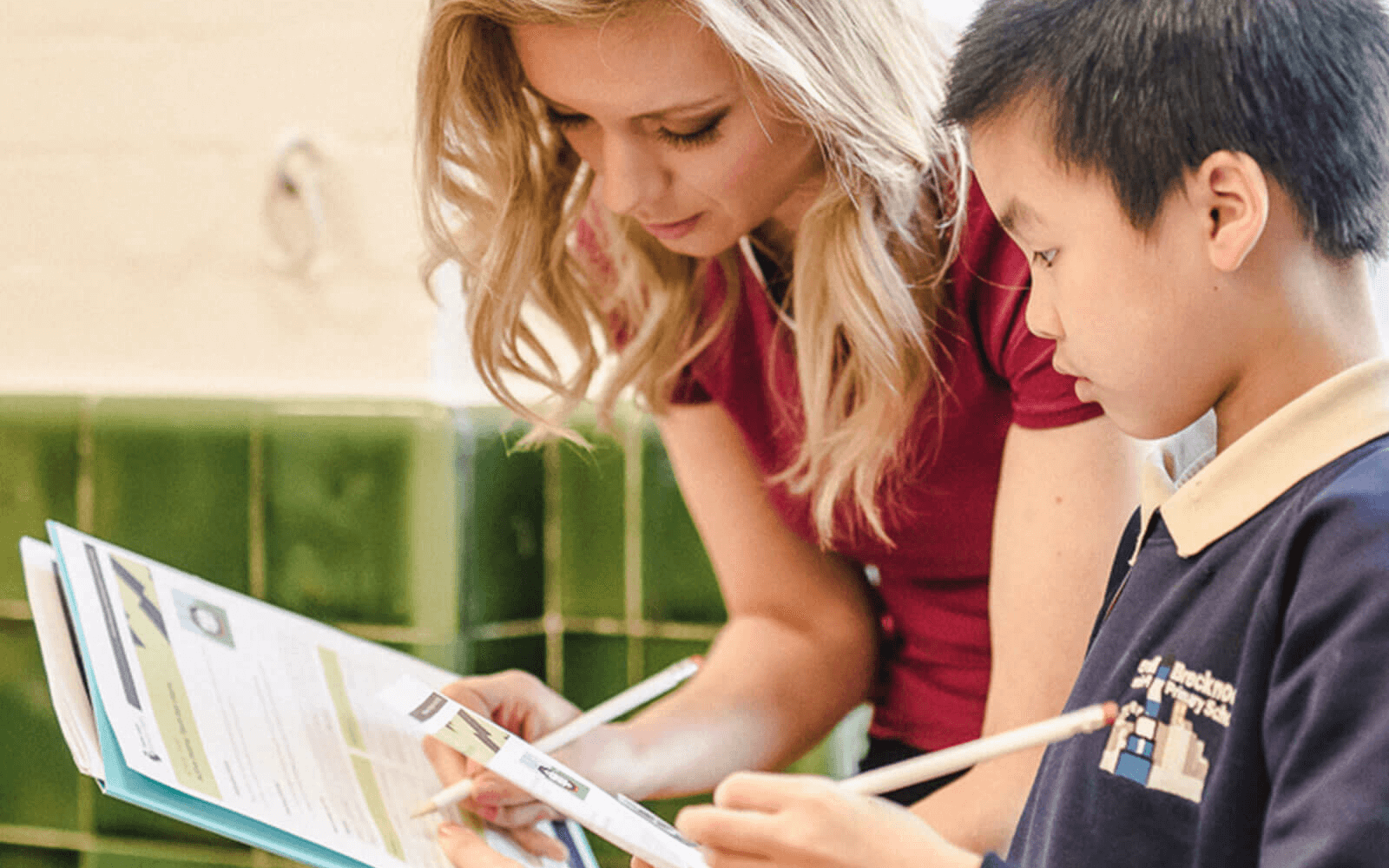 Image showing Rachel Riley aiding a pupil in their maths work during a lesson
