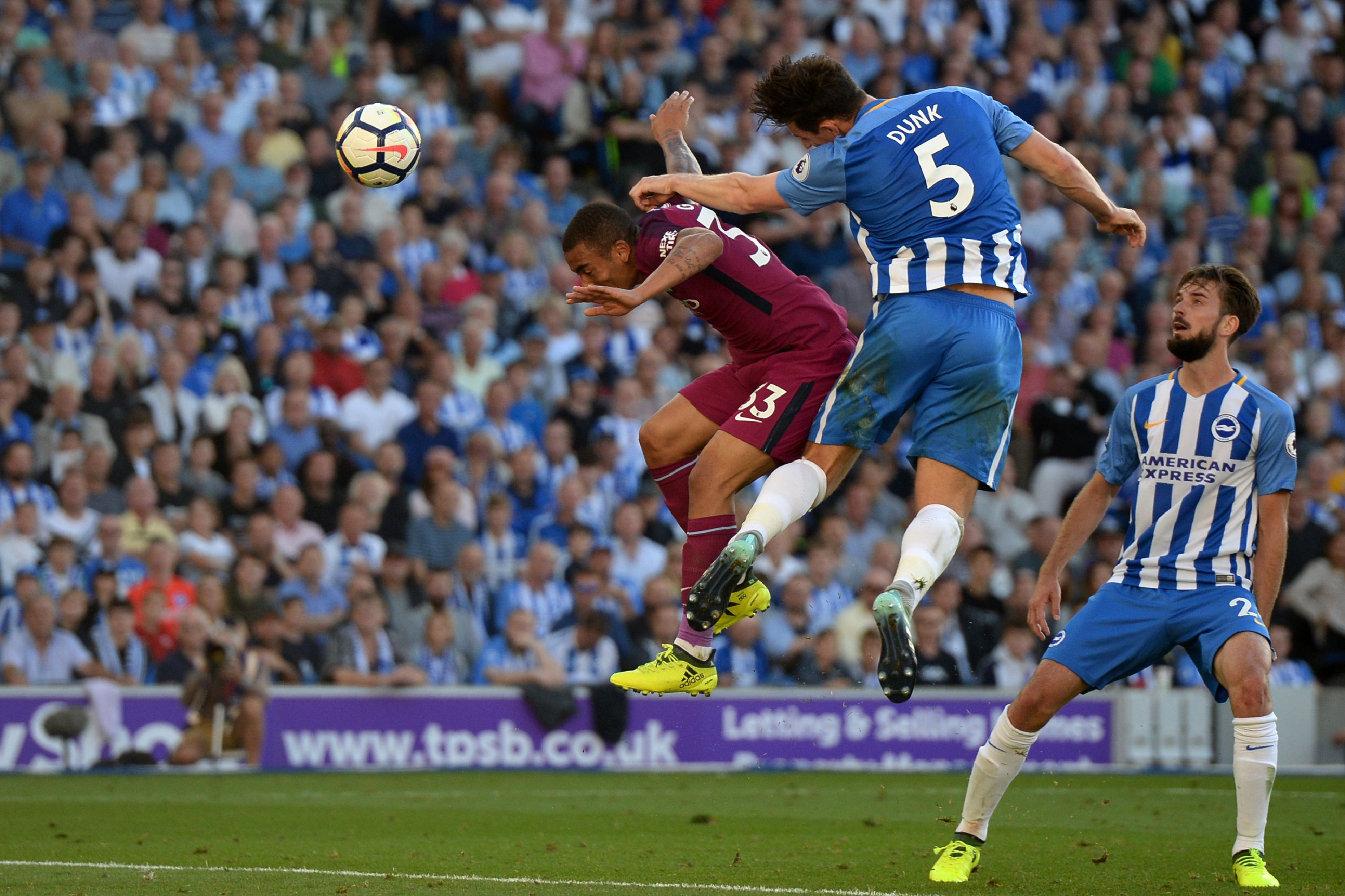 Brighton and Manchester City players jump for the ball