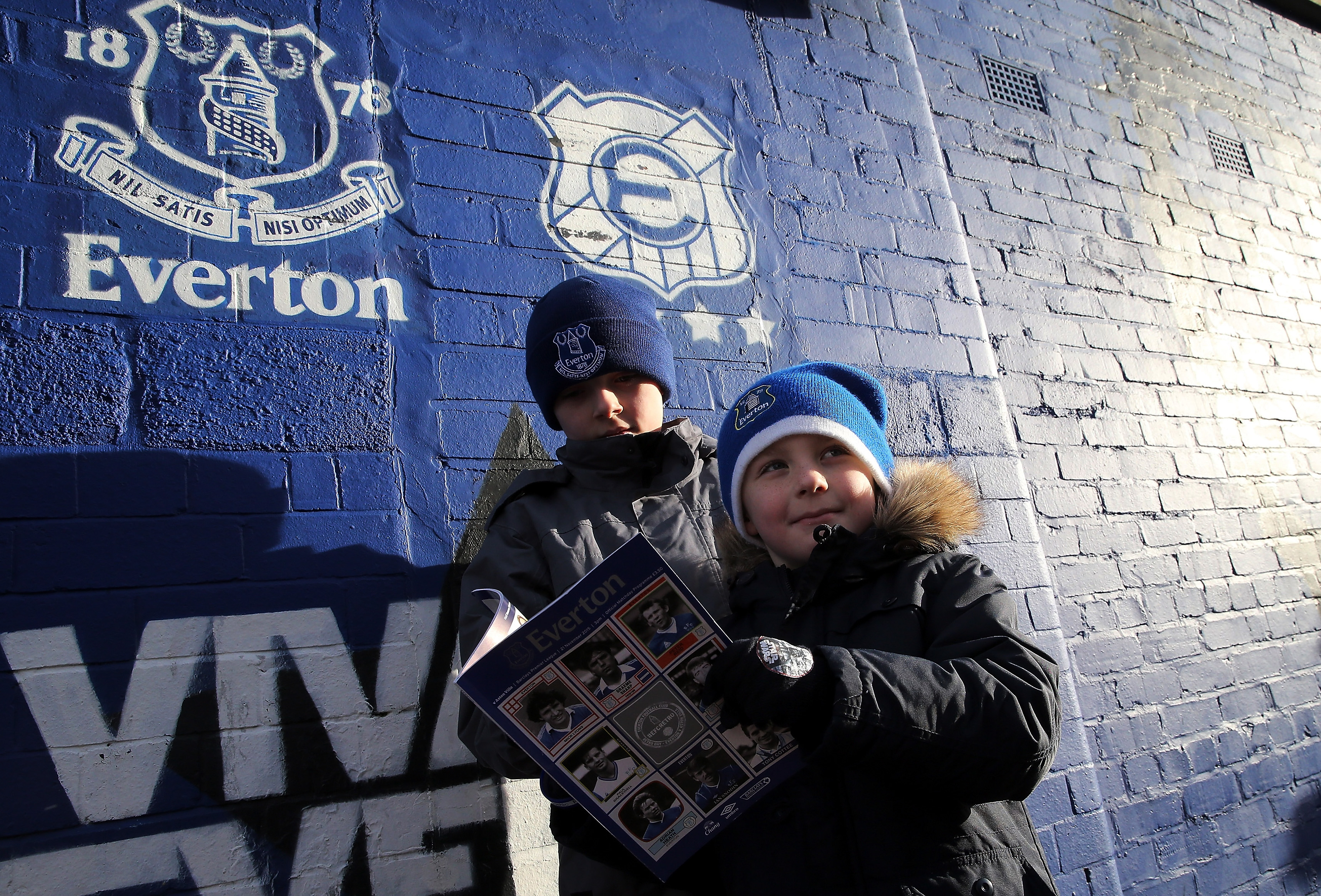 Young Everton fans reading a match programme
