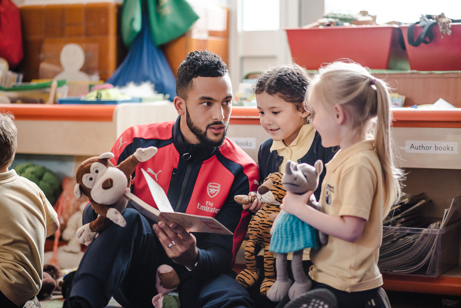 Theo Walcott reads with a group of children