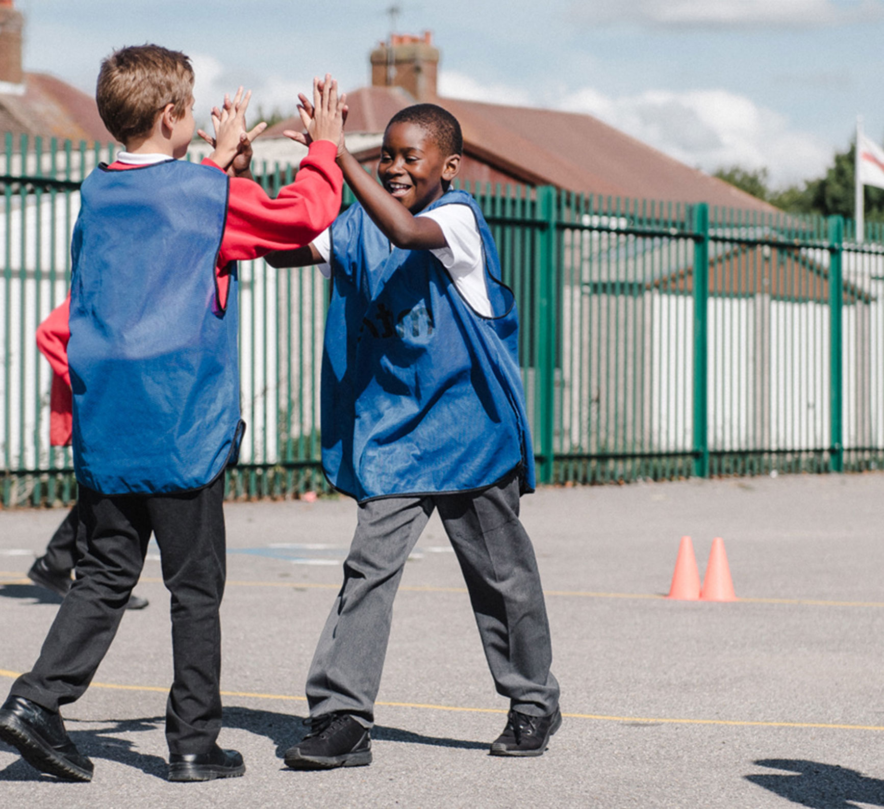 Two boys high five in the playground